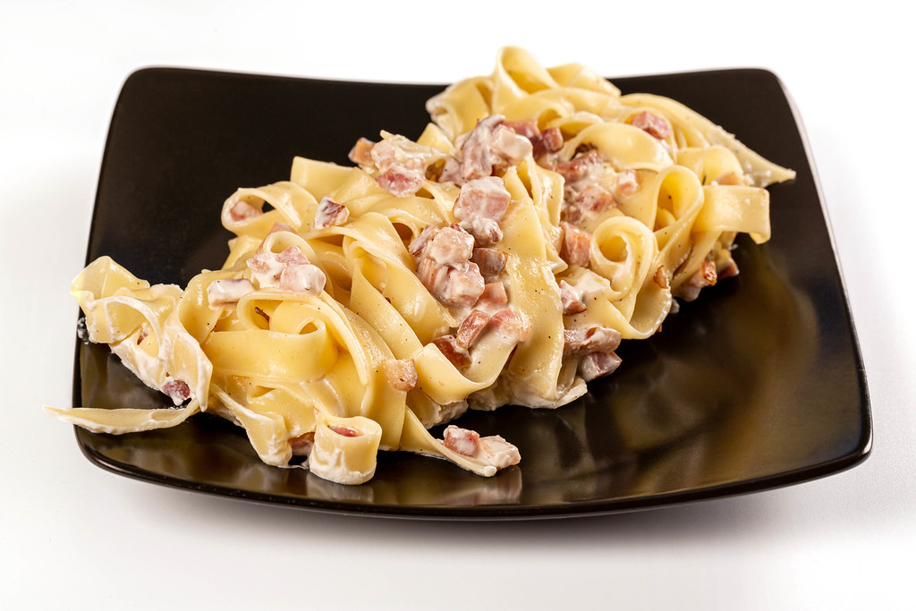Carbonara pasta with creamy sauce, bacon and ham on a black plate