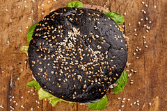 Top view, black burger on wooden board