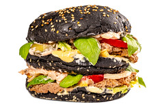 Beef burger with a black bun, lettuce,basil, sauce and vegetables