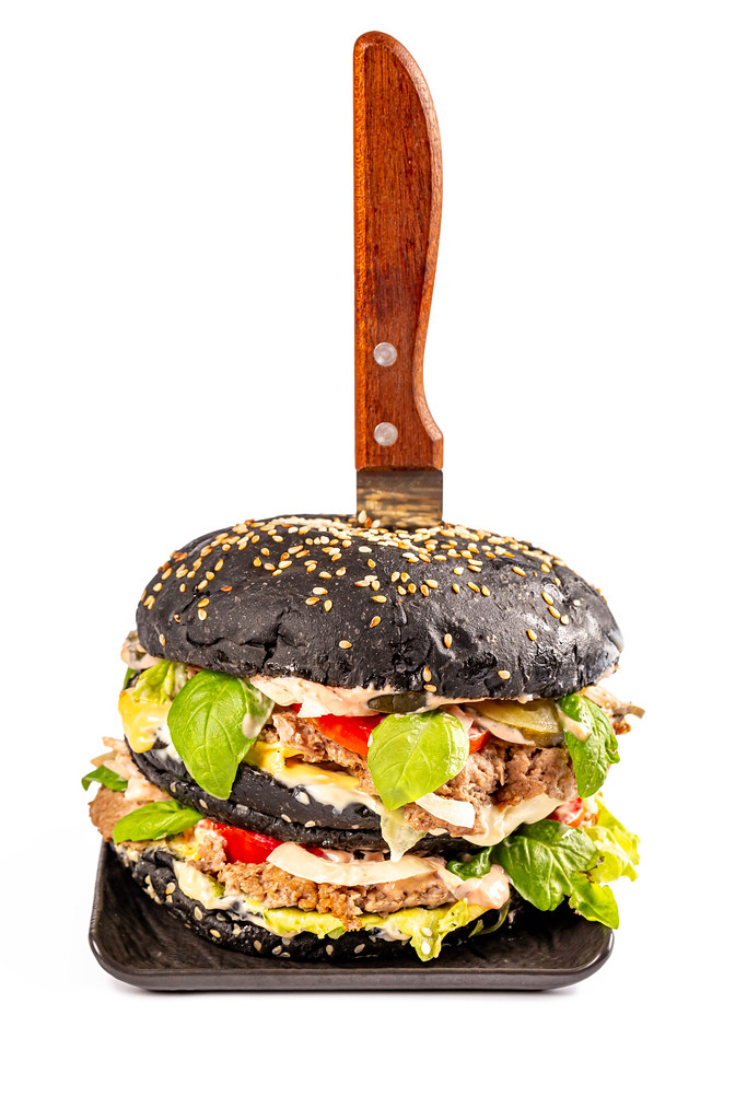 Big black burger with knife on white background