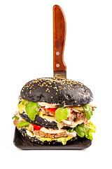 Big black burger with knife on white background