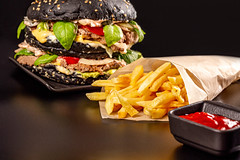 Delicious black burger with vegetables, cutlet and cheese on a dark background with fries and sauce