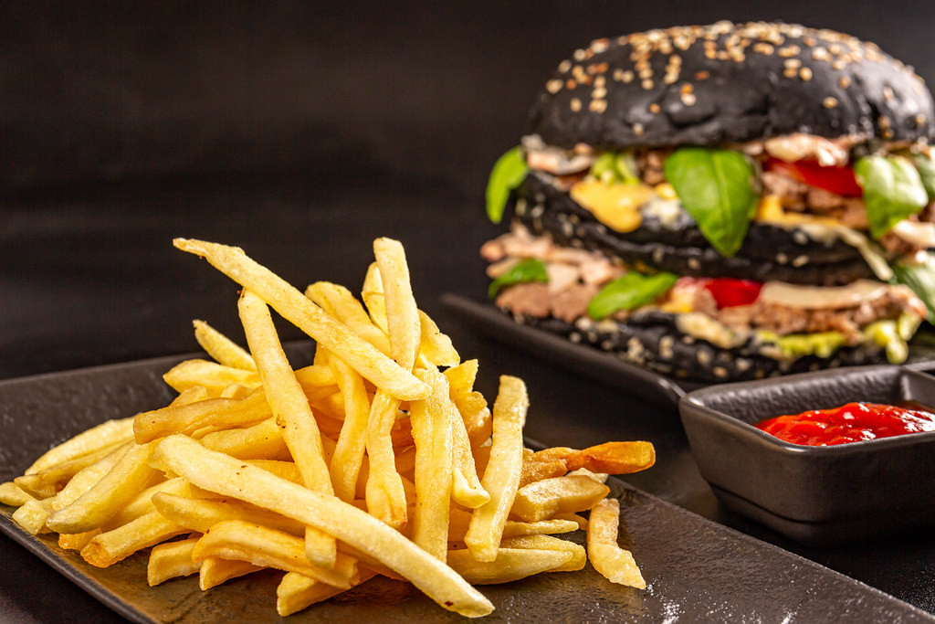 Delicious junk food background - french fries and black burger