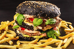 Close-up, black burger with two cutlets, cheese, vegetables and herbs and french fries