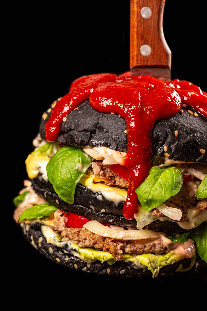 Close-up, black burger with a knife and a spicy red sauce