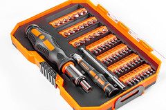 A set of screwdrivers and bits in an orange box