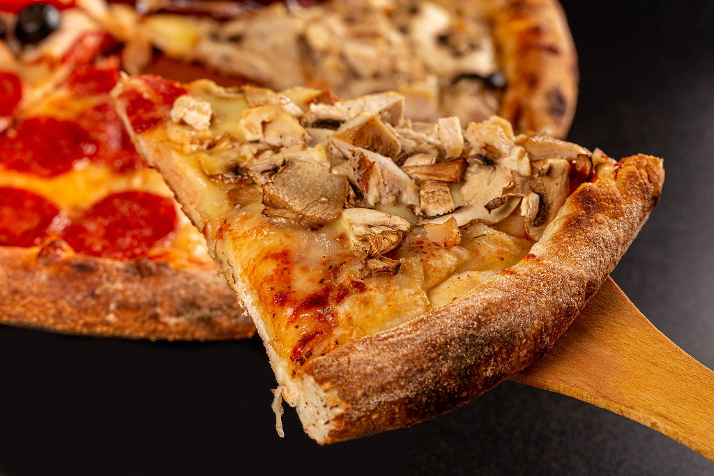 Close-up, slice of pizza with mushrooms and cheese on wooden spatula