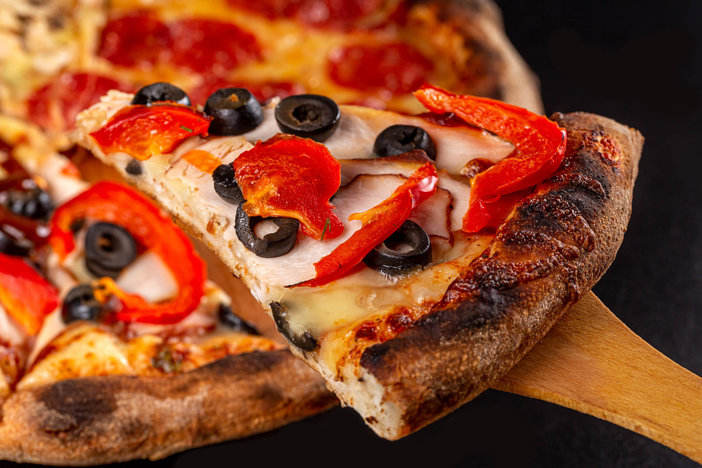 Close-up, slice of pizza with ham, bell pepper and black olives