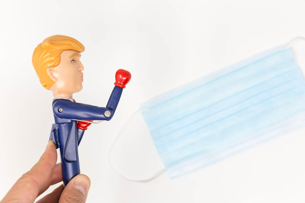 US-Covid-crisis - Donald Trump pen stretches his arm forward with a red boxing glove in front of face mask