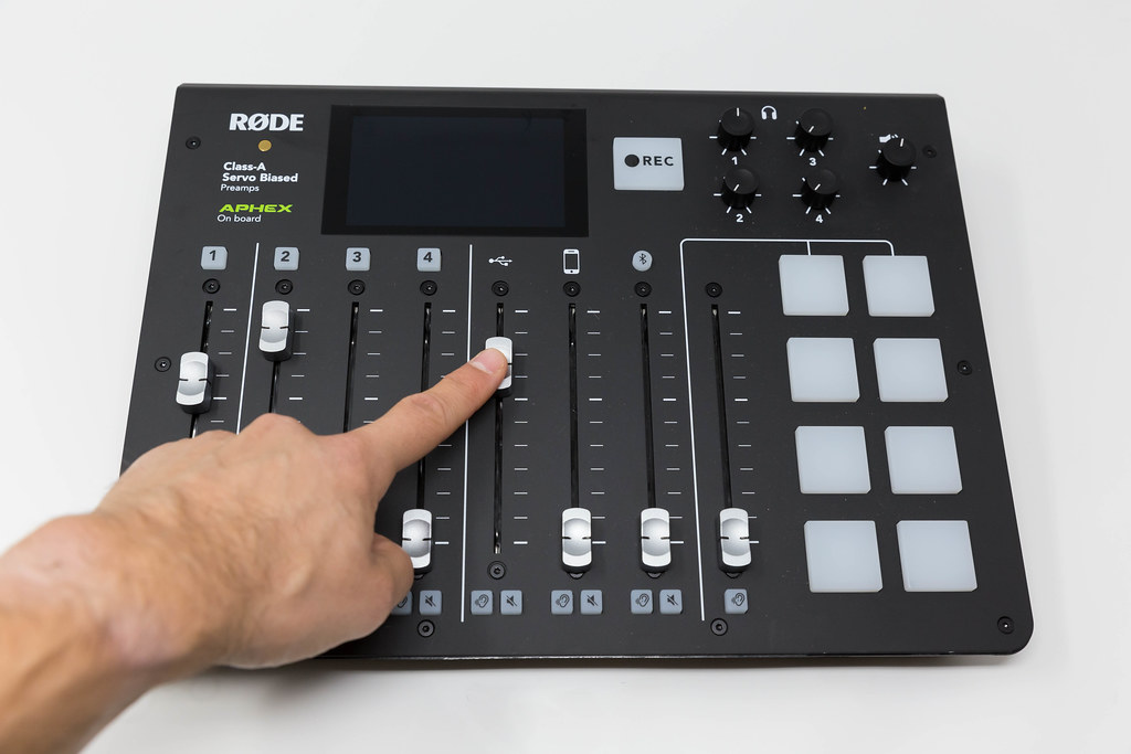 Hand adjusts the RØDECaster Pro, the world's first fully integrated podcast production studio