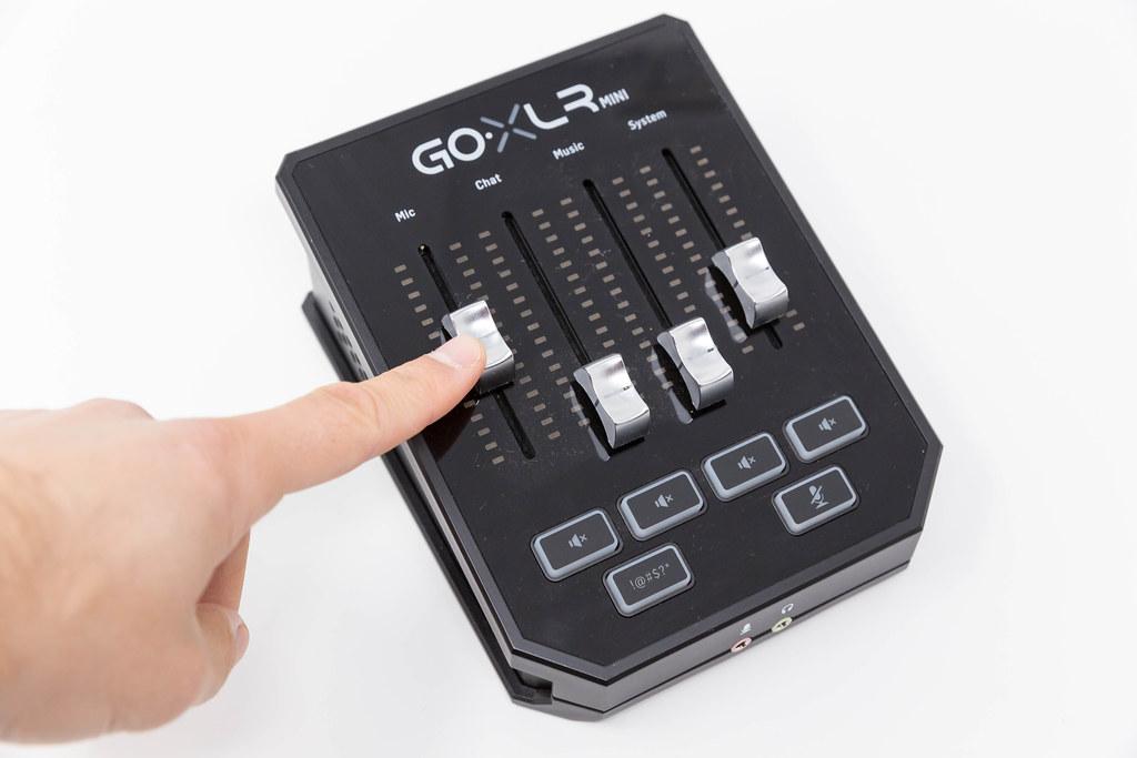 Finger auf schwarzem Online Broadcast Mixer Go XLR Mini von TC-Helicon. Podcast-Ausrüstung