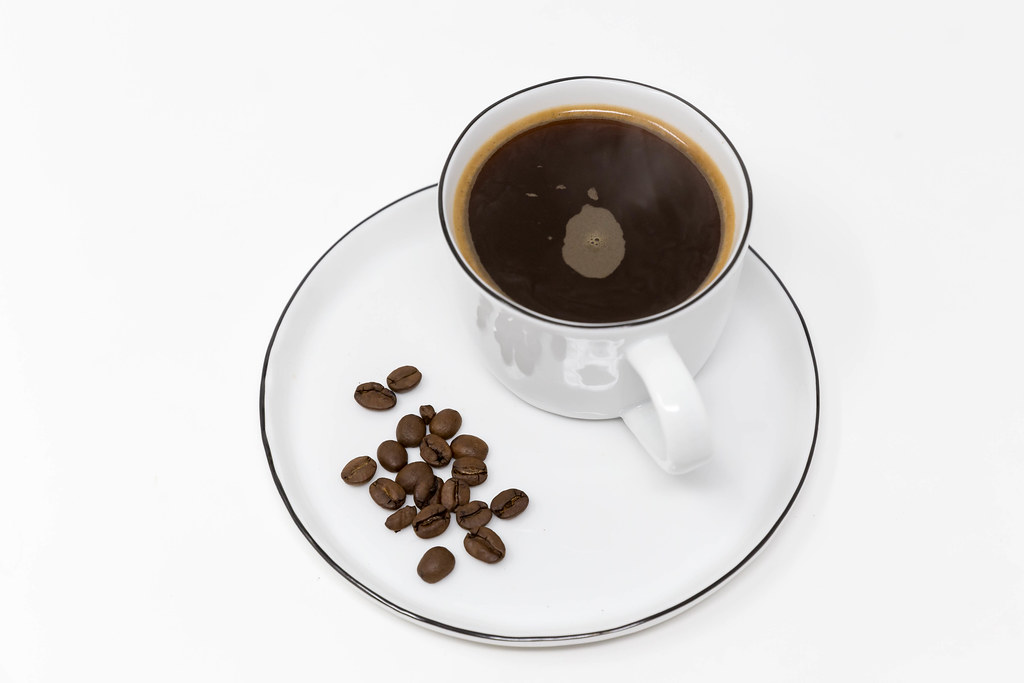 Good morning with a black coffee in a white cup with coffee beans on a white plate on white background