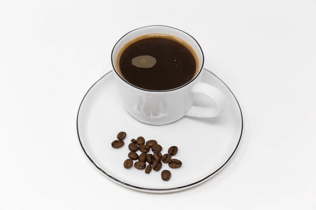 Black coffee cup with no milk served on a white plate with decorative coffee beans and white background
