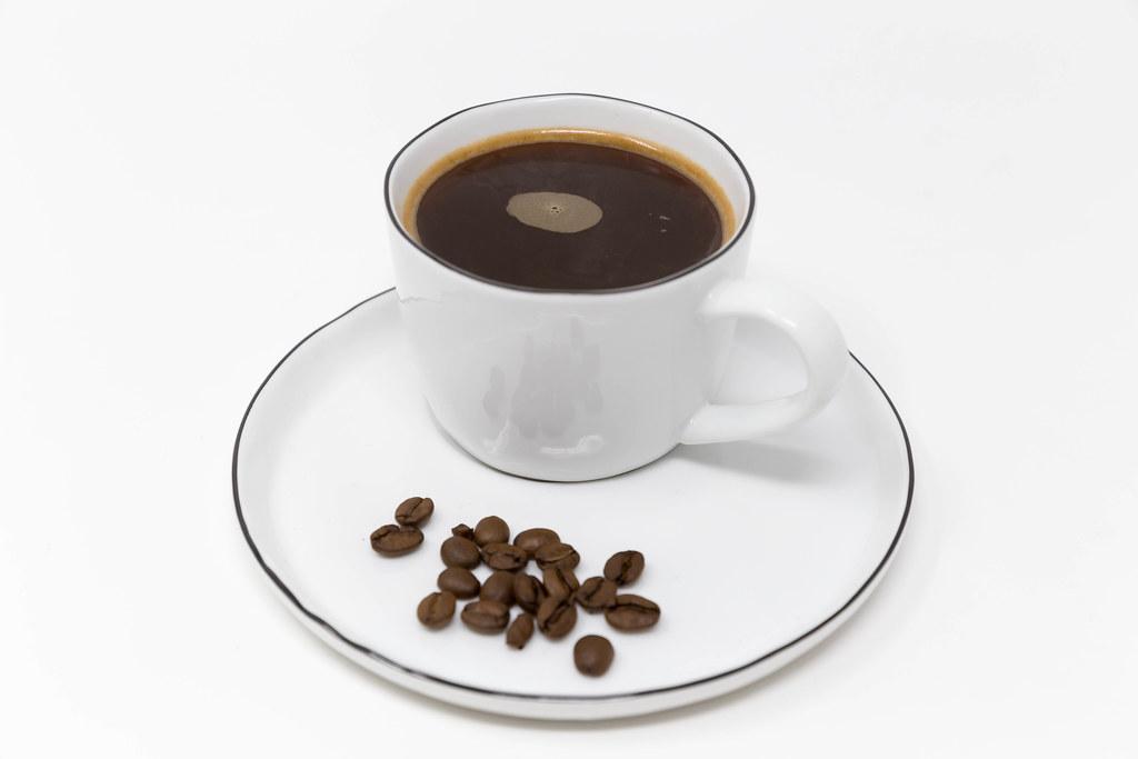 Nahaufnahme einer Tasse schwarzer Kaffee auf einem weißen Teller mit Kaffeebohnen serviert