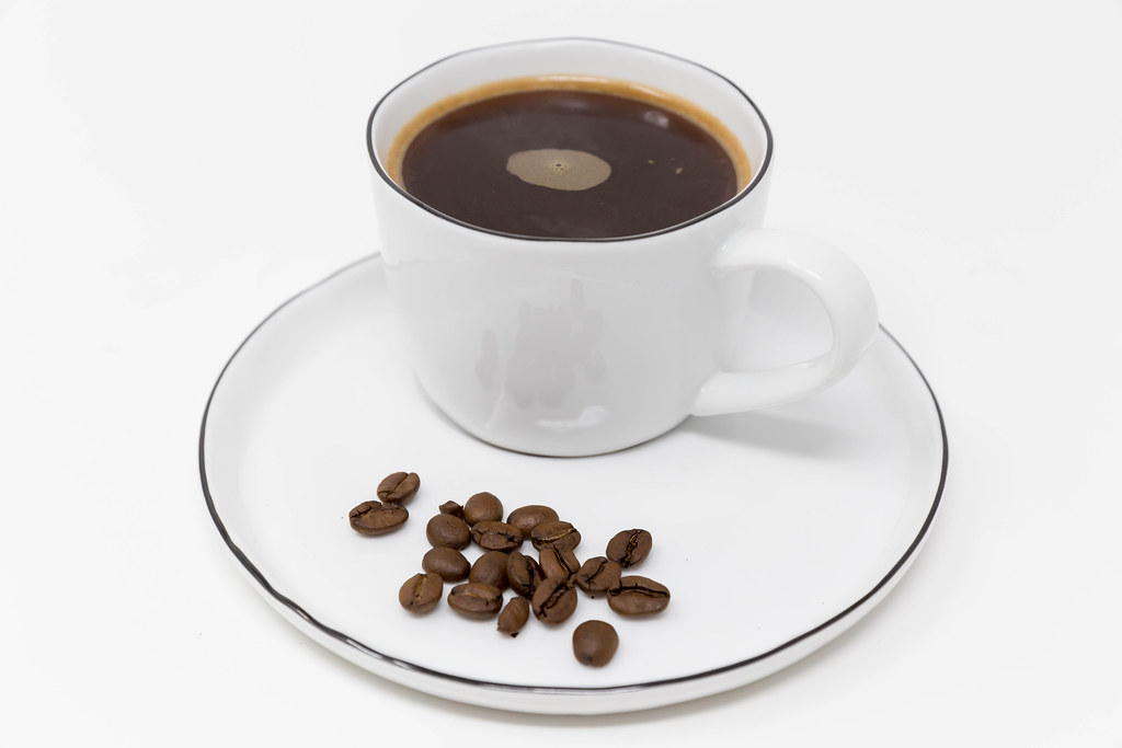 Close-up of coffee beans on a white plate with a black coffee in a white cup as an energy boost