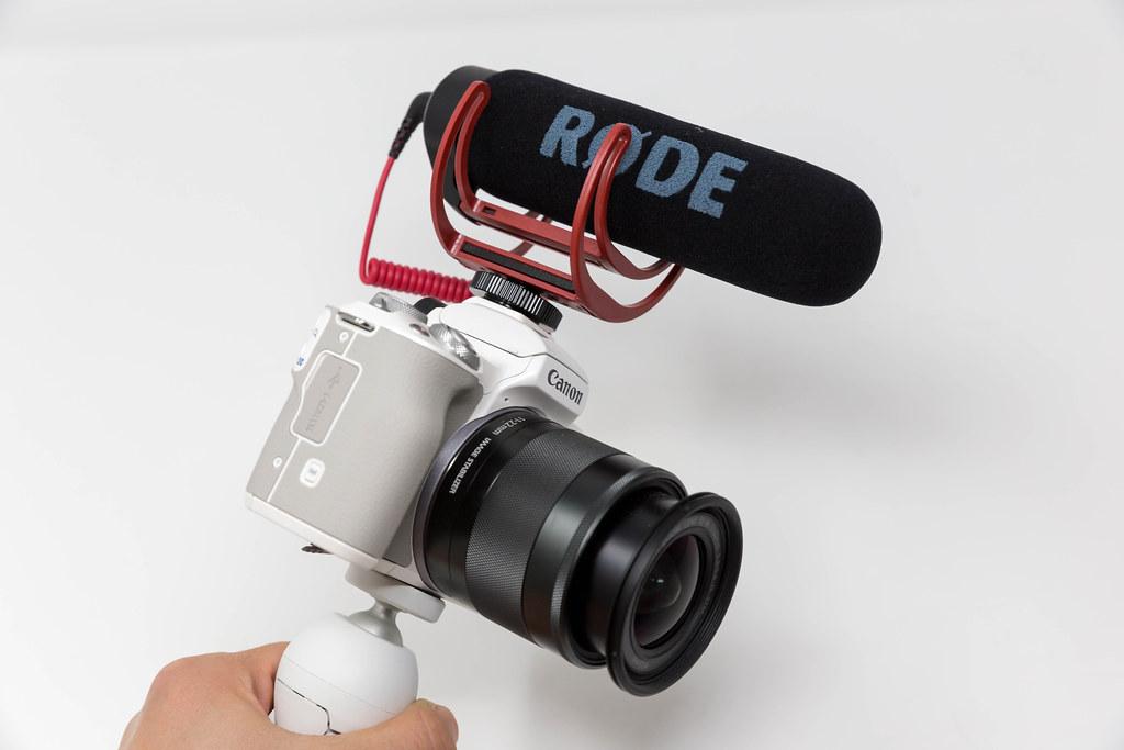 Hand hält eine Canon DSLR Kamera mit RØDE kompaktem Mikrofon vor weißem Hintergrund