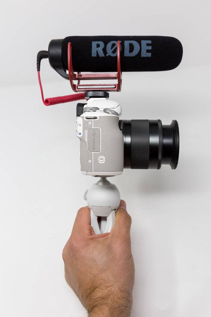 Männliche Hand hält eine Canon Kamera mit RØDE kompaktem Außenmikrofon - Seitenansicht