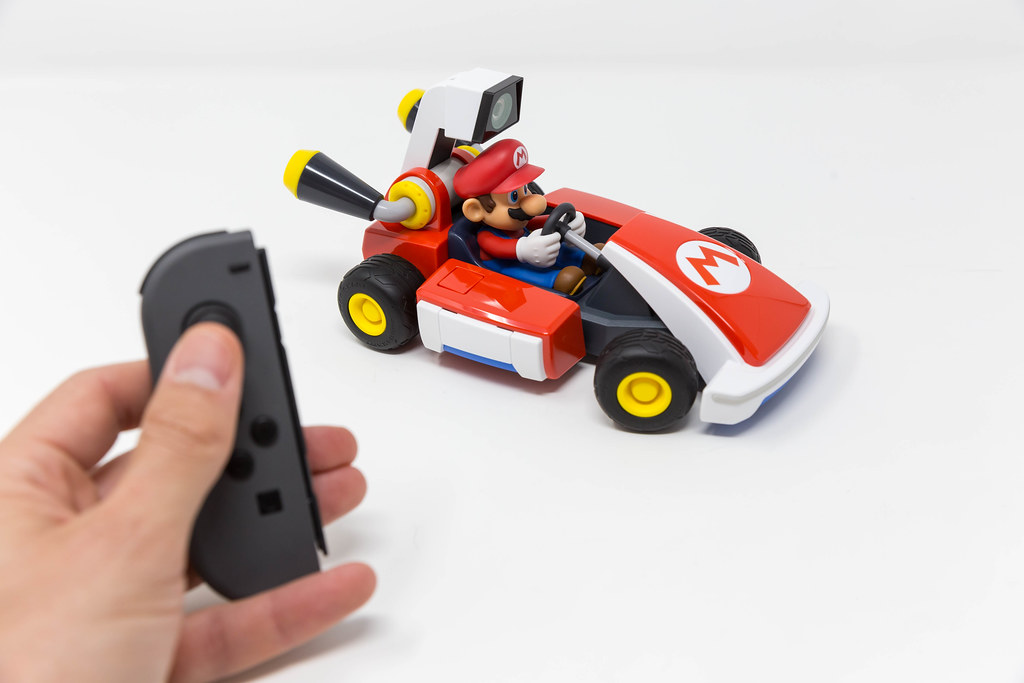 Male hand pushes a button on Nintendo Switch to get the race begin with the Mario Kart