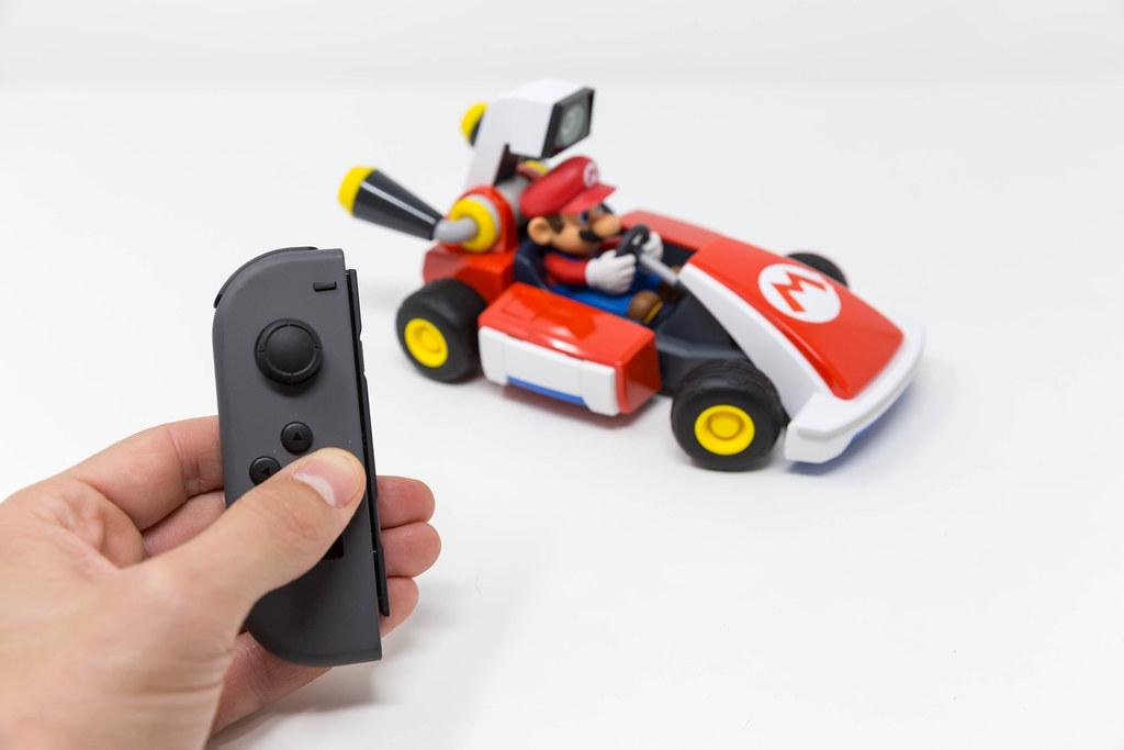 Männliche Hand drückt ein Button auf Nintendo Switch, um das Rennen mit dem Mario Kart zu starten