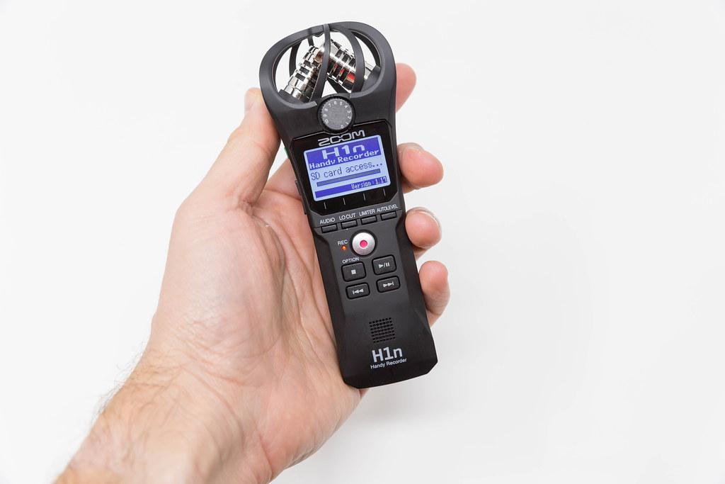 Nahaufnahme einer Hand, die den Handy-Recorder Zoom H1n hält. Zugriff auf SD Karte