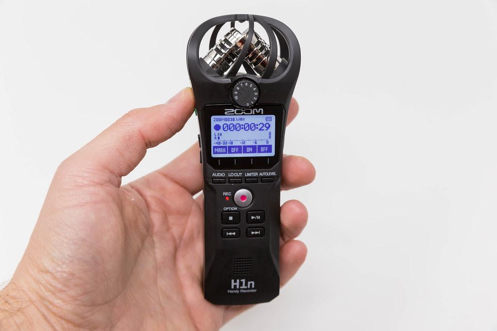 Hand hält den Zoom H1n Handy Recorder während eine Aufnahme auf dem Display angezeigt wird