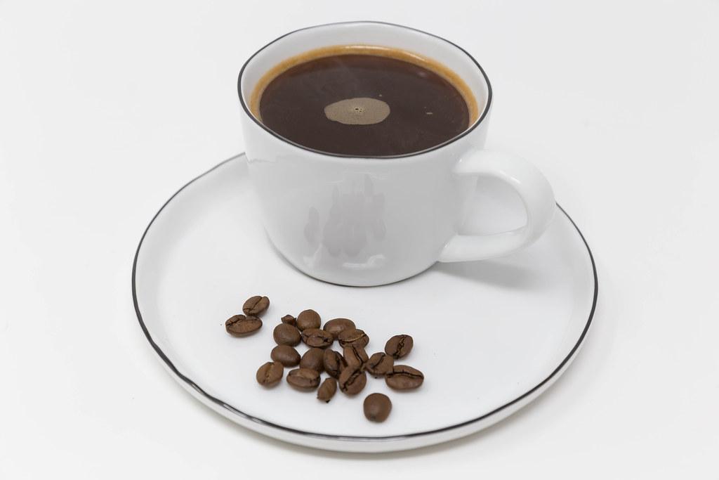 Nahaufnahme: Kaffeebohnen mit einer Tasse ganz normaler Kaffee ohne Milch vor weißem Hintergrund