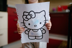 Young girl holding a piece of paper from a coloring book.