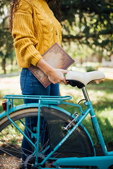 Close up of a woman holding a book while holding a bicycle by it's seat.