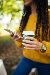 Woman with curly hair and yellow sweater holding a cup of coffee in one hand and her phone in other.