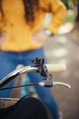 Close up of a bell on the bicycle handle and a woman in the background.