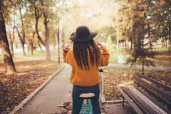 Woman with black hat fixing her hair while sitting on a bike near the wooden bench in the park.