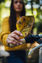 Close up of an autumn leaf in a woman's hand.