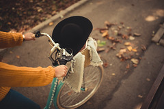 Woman in a yellow sweater riding a bicycle in the park covered with falling leaves.