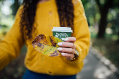 Woman in yellow sweater holding a green cup of coffee and a leaf in her hand.