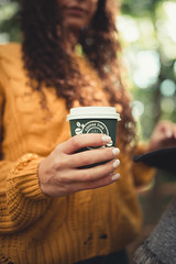 Woman with curly hair holding a green cup of coffee in her hand.