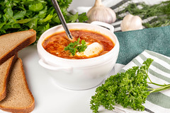 Vegetable tomato soup with sour cream and herbs