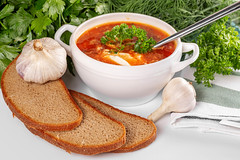 A bowl of borscht with sour cream, black bread, fresh garlic, dill and parsley