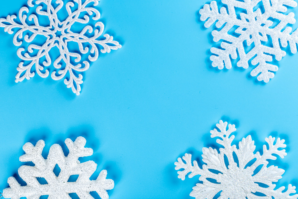 Christmas background with white snowflakes on blue