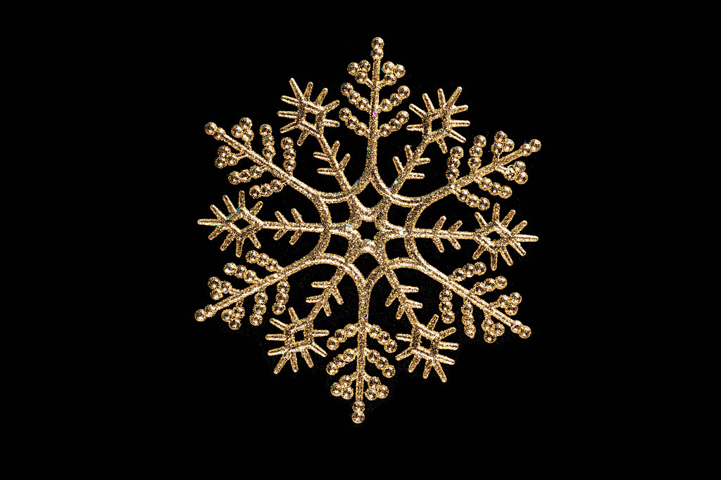 Golden Christmas snowflake on black background