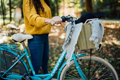Woman in a yellow sweater holding a bicycle in a park.