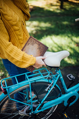Woman holding a book while resting her arm on a bicycle seat.