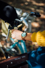 Close up woman holding a bike handle with a stylish watch on her hand.