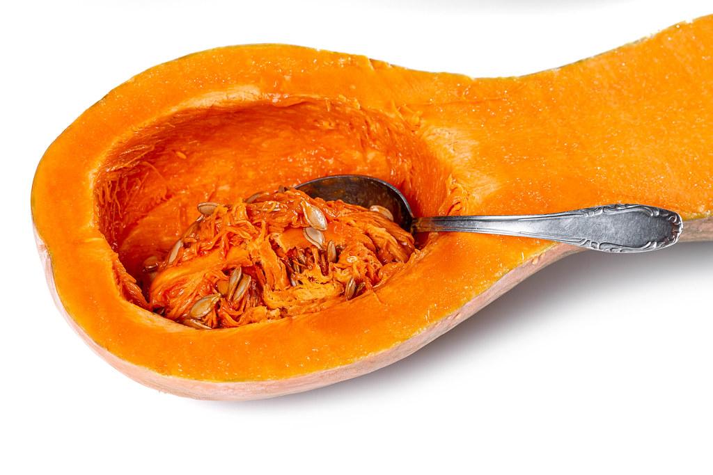 Fresh raw half orange pumpkin with seeds and spoon