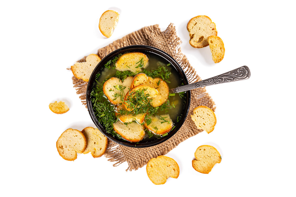A bowl of soup with croutons and dill on a white background, top view