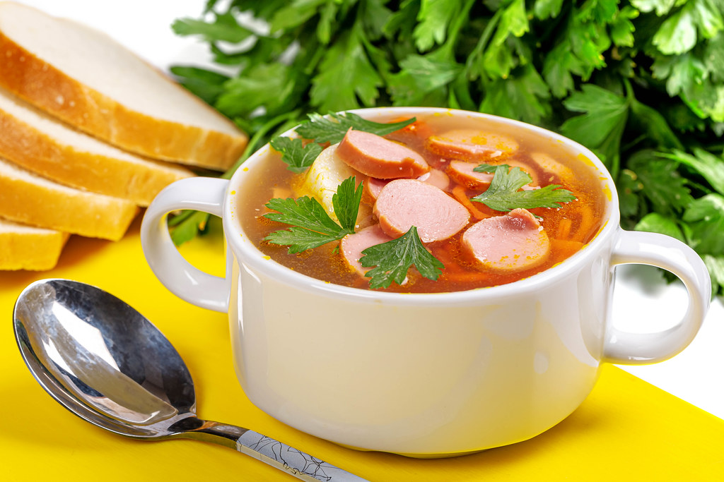 Carrot and onion soup with sausages on yellow kitchen board