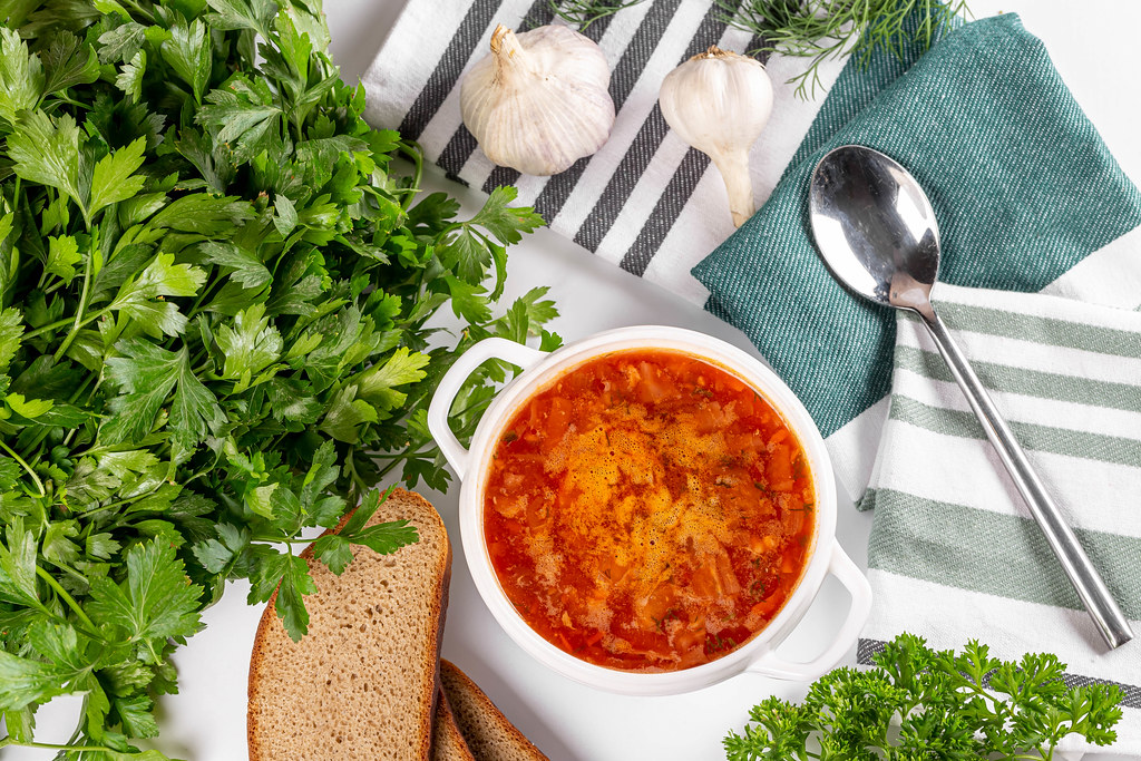 Top view, hot borsch with garlic, herbs and black bread