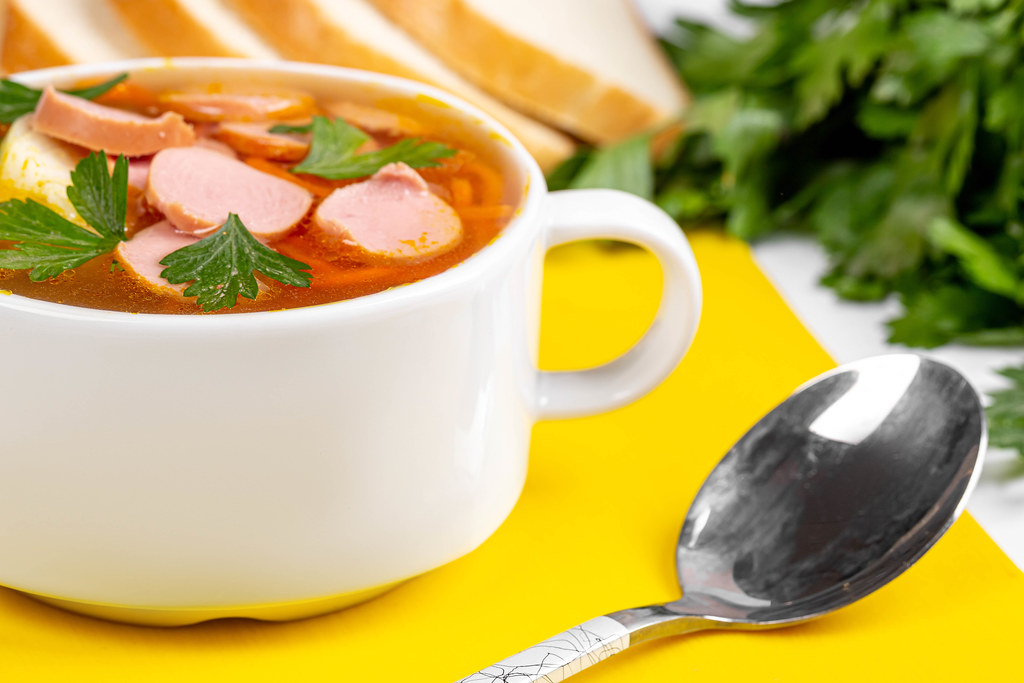 Delicious soup with carrots, onions and pieces of sausages