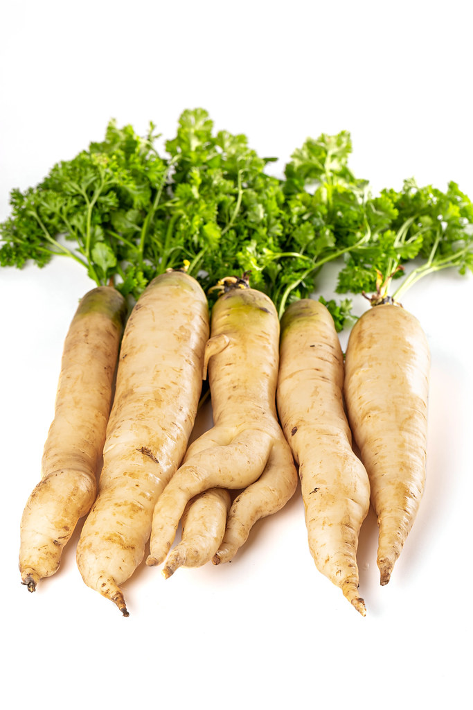 Ripe raw white carrots with green leaves