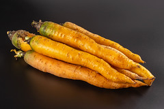 Raw organic yellow carrots on black
