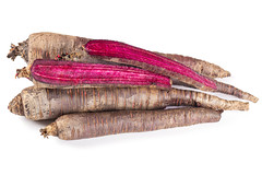 Whole and halves purple carrots on white background